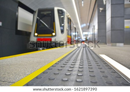 Concrete tactile strips with an yellow line - for visually impaired (handicapped) and people with blindness - on an underground station, with a blurred arriving subway train and background Zdjęcia stock ©