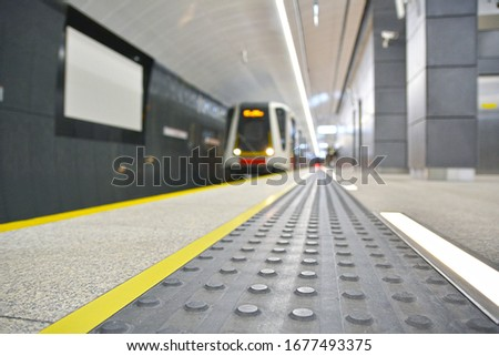 Concrete tactile strips with an yellow line - for visually impaired (handicapped) and people with blindness - on an underground station, with a blurred train in the background Zdjęcia stock ©