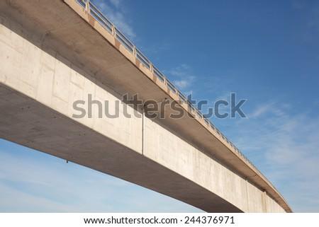 Concrete traffic bridge span and blue sky.