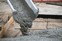 Concrete Truck Chute Pouring Wet Cement Mix into a Form with Reinforcing Bar for a Sidewalk