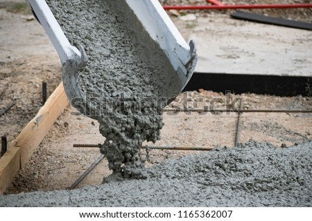 Concrete Truck Chute Pouring Wet Cement Mix into a Form with Reinforcing Bar for a Sidewalk #1165362007