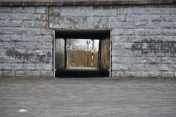 Concrete tunnel in the bridge. Building construction in the wall. Passage under the old bridge. Square hole under the road.