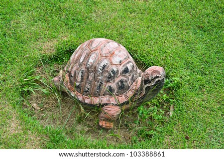 Concrete turtle on the green grass.