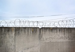 Concrete wall, against the backdrop of barbed wire, the concept of prison, salvation, Refugee, lonely, space for text