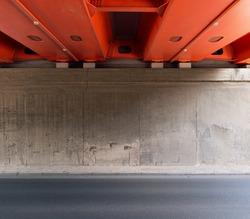 Concrete wall and asphalt road under the bridge.