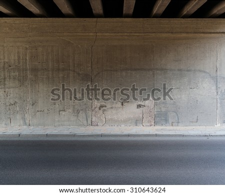 concrete wall and asphalt road...