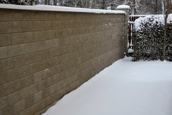 concrete wall from texture blocks. high dividing noise wall of the yard. The wall is equipped with a sheet metal roof, which prevents water from flowing into the body of the wall and tearing by frost.
