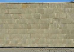 concrete wall made of smooth blocks. high dividing noise wall of the yard. under the wall is a longitudinal channel with a grid for drainage interlocking paving