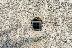 Concrete wall with a metal lattice in a small hole