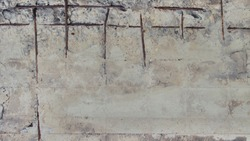 Concrete wall with rusty reinforcement rods background.Texture of old gray concrete wall for background