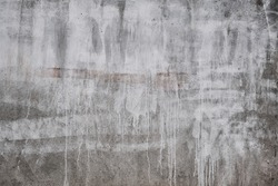 Concrete wall with white dripping paint, grunge background or texture
