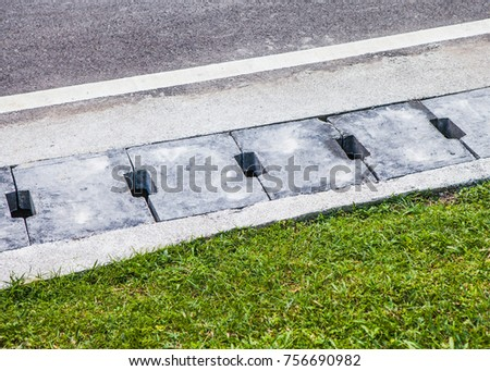 Concrete Water Drain Cover Or Ditch On The Road With Green Grass #756690982