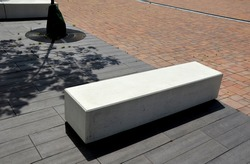 concrete white park bench block shape on dark paving square, clean cast concrete surface gray brown white light barrier against traffic terrorism pedestrian zone