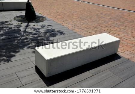 concrete white park bench block shape on dark paving square, clean cast concrete surface gray brown white light barrier against traffic terrorism pedestrian zone