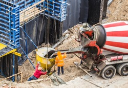 Concreting work at the construction site. Construction workers pour liquid concrete into cement concrete hopper from concrete mixer at the construction site of a large residential building.
