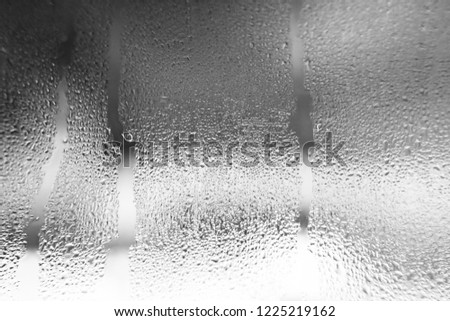 Condensate on the glass is black, moist texture of water, steam, rain outside the window. Natural background. Abstract wallpaper