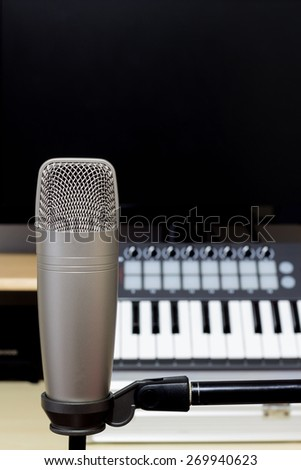condenser microphone , music synthesizer keyboard & black monitor in recording studio / copy space on top for music concept