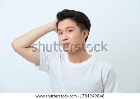 Condifent young asian man with stylish haircut and appealing eyes, touching dark hair, posing against white background