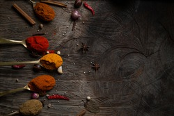 Condiment of mix indian food explosion Spice splash dark background on wood table top view. Desk Asian organic herb cuisine flavour in kitchen board, chilli spicy powder in brass spoon concept
