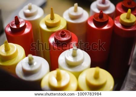 condiments of mustard, mayonnaise, ketchup and hot sauce on a hot dog cart