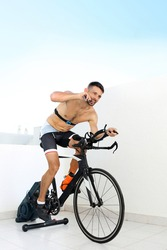 Conditioner during training. The athlete eats an energy bar riding a stationary bike Sports training on a stationary exercise bike.