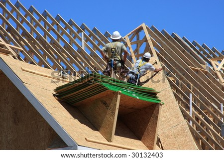 Condo construction with workers on the roof frame