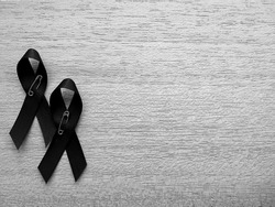 Condolences black ribbon to show the sorrow and the sadness on the passing or the death of people. Closeup ribbon on the black and white background.