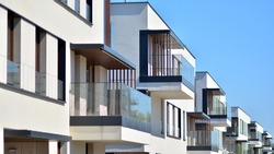 Condominium and apartment building with  symmetrical modern architecture. Detail in modern residential flat apartment building exterior. Fragment of new luxury house and home complex.