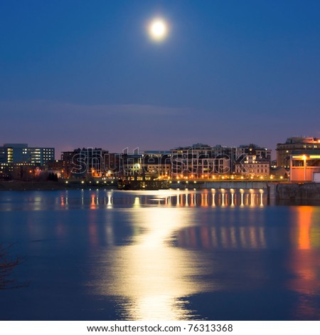 Condominium and office building in Old Montreal, with a reflection of the silhouette of the moonlight in the water at dusk
