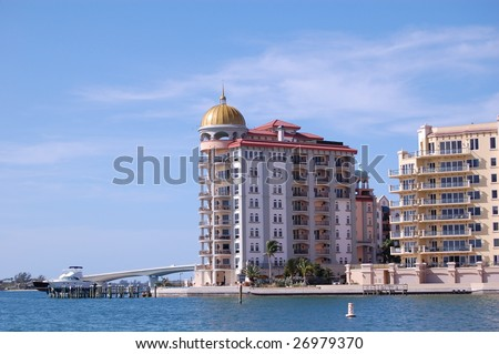 Condominium on sarasota bay in florida with the ringling bridge in the background and a yacht in front.