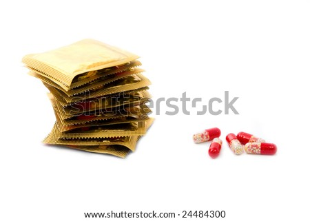 Condoms in a stack and oral contraceptive pills isolated on white