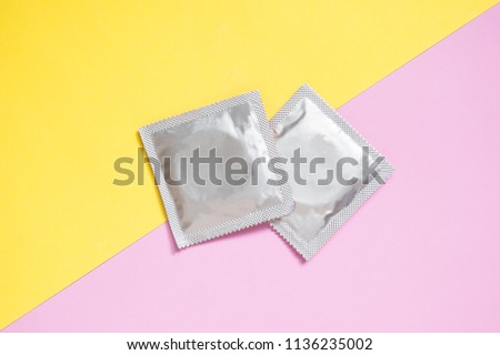 Condoms package on yellow pink background. A condom use to reduce the probability of pregnancy or sexually transmitted disease (STD). Safe sex and reproductive health concept.