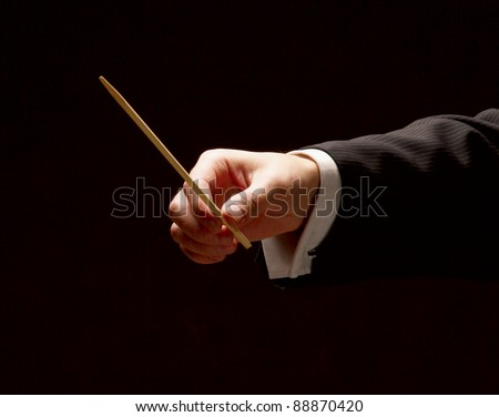 Conductor conducting orchestra isolated on black background