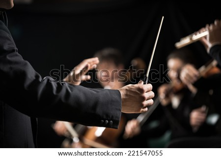 Conductor directing symphony orchestra with performers on background, hands close-up. Foto stock ©