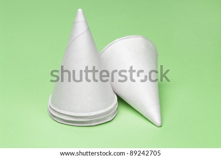 Cone shape disposable paper cups on green background