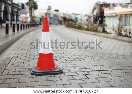 cone sign on the road. Striped orange cones on the asphalt road. Plastic orange cone on the road.Traffic cone on a parking lot in the park. traffic cone, with white and orange stripes on gray asphalt