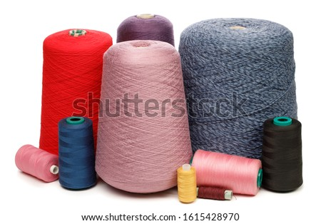 Cones and spools of synthetic or cotton threads on white background. Spool of yarn using for weaving in textile manufacturing