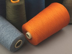 Cones of colored cotton, woolen or synthetic threads. Bobbins of yarn using in textile manufacturing and for handmade products, copy space