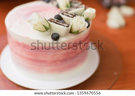 confectioner decorates a beautiful cake with roses, blueberries and biscuits