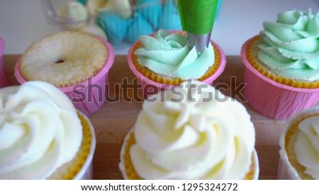 Confectioner decorates muffins with cream