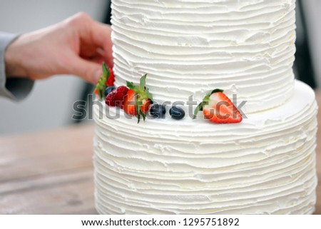 Confectioner decorates white wedding cake