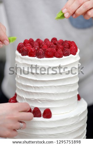 Confectioner decorates white wedding cake