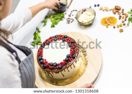Confectioner decorates with berries a biscuit cake with white cream and chocolate. Cake stands on a wooden stand on a white table. The concept of homemade pastry, cooking cakes.