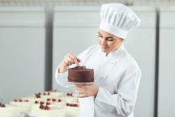 Confectioner decorating chocolate cake in pastry shop.