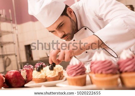 confectioner decorating cupcakes in restaurant kitchen