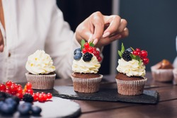 Confectioner decorating top cupcake with glazed currant before serving