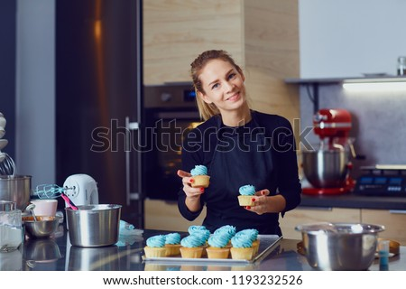 Confectioner pastry woman holding a tray of cupcakes.