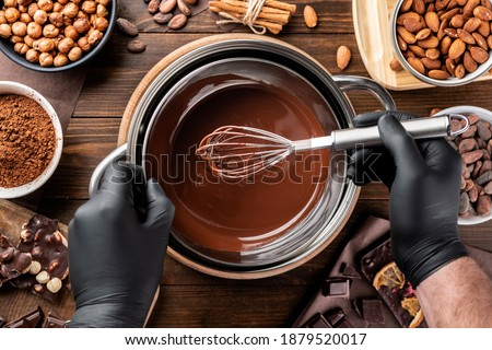 Confectioner stirring melted dark chocolate in a bowl, top view, close-up. Liquid hot chocolate. Confectionery preparation. Melted chocolate preparation