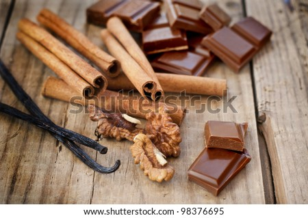 confectionery products. Chocolate, cinnamon, walnuts and vanilla on wooden table