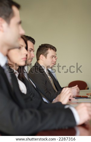 conference, group of 5 business people sitting at the big table  -close up